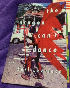The cover of The Dragon Can't Dance, which reatures white text over a photo of a Black man dressed as a devil with red wings and body paint